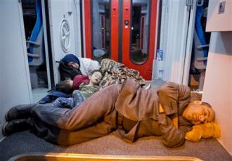Migrantes descansan en un tren en la estación de Beli Manastir, cerca de la frontera húngara, en el nordeste de Croacia, en la madrugada del viernes 18 de septiembre de 2015.  Croacia se ha convertido en el nuevo punto caliente del éxodo de más de 1.000 milllas de los migrantes que tratan de llegar a la Europa occidental, después de que Hungría sellara su frontera el martes y después chocara con migrantes para mantenerlos alejados. (AP Foto/Darko Bandic)